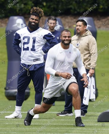Dallas Cowboys running back Ezekiel Elliott (21) looks on as quarterback Dak Prescott warms-up during an NFL football team practice, in Frisco, Texas