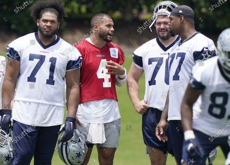 Dallas Cowboys quarterback Dak Prescott (4) speaks with offensive linemen Zack Martin (70), Tyron Smith (77), and La'el Collins (71) during an NFL football team practice, in Frisco, Texas