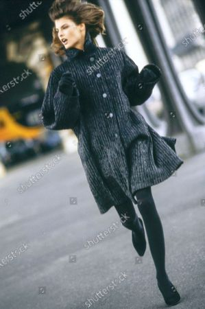 Model Linda Evangelista, on a street in Paris, France. She is wearing a knee-length flared gray wool coat textured with vertical black rubber stripes and black wool gloves, both by Azzedine Alaia. Hair by James Bradshaw for Jean Louis David. Makeup by Mary Greenwell.