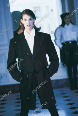 Model Linda Evangelista in the Saint James & Albany Hotel in Paris, wearing a black wool cropped tuxedo jacket with matching knee-length shorts over a white cotton blouse, from Comme des Garcons by Rei Kawakubo. Hair by James Bradshaw for Jean Louis David. Makeup by Mary Greenwell.