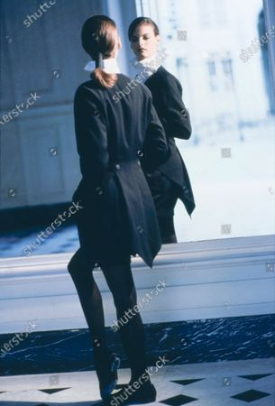 Model Linda Evangelista by a mirror in the Saint James & Albany Hotel in Paris,  wearing a short black wool tailcoat with matching shorts over a white blouse by Issey Miyake. Hair by James Bradshaw for Jean Louis David. Makeup by Mary Greenwell.