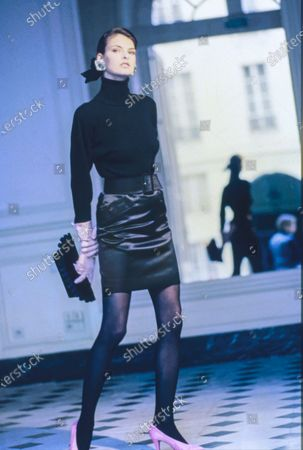 Model Linda Evangelista in the Saint James & Albany Hotel in Paris, wearing a black ribbed wool turtleneck and a black silk satin skirt with a wide belt, with pink satin shoes and suede gloves, by Saint Laurent Rive Gauche. Hair by James Bradshaw for Jean Louis David. Makeup by Mary Greenwell.