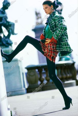 Model Linda Evangelista on a bridge in Paris, France, with arms akimbo and one leg braced against a wall. She is wearing a white-on-green plaid jacket and a white-on-red plaid miniskirt (both of wool) belted by a gold chain, over a green cashmere sweater, with red gloves, black high-heeled shoes, and gold earrings inset with black enamel and a large pearl, all by Chanel. Stockings by La Leg. Hair by James Bradshaw for Jean Louis David. Makeup by Mary Greenwell.