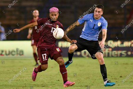 Venezuela's Josef Martinez and Uruguay's Jose Gimenez battle for the ball during a qualifying soccer match for the FIFA World Cup Qatar 2022 in Caracas, Venezuela