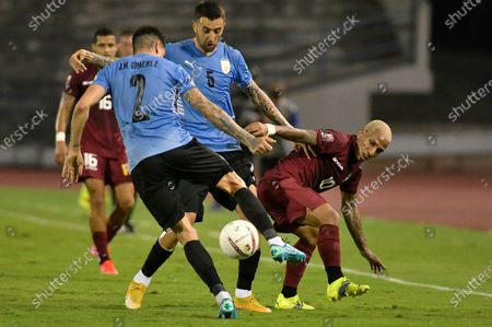 Venezuela's Romulo Otero, right, and Uruguay's Jose Gimenez, left, battle for the ball during a qualifying soccer match for the FIFA World Cup Qatar 2022 in Caracas, Venezuela