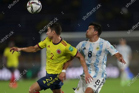 Colombia's Stefan Medina, left, and Argentina's Marcos Acuna eye the ball during a qualifying soccer match for the FIFA World Cup Qatar 2022 at the Metropolitano stadium in Barranquilla, Colombia