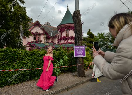 Visitors take photos in front of the house in The Burnaby area of Greystones which has been covered from the roof down by stretched pink flowers and trellis-style foliage ahead of Disney's 'Disenchanted' filming starting next week.On Tuesday, 8 June 2021, in Greystones, County Wicklow, Ireland.