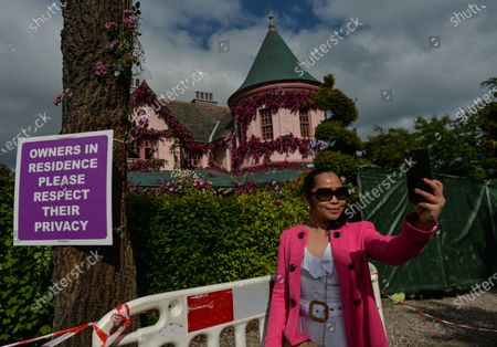 A visitor takes a selfie outside the house in The Burnaby area of Greystones which has been covered from the roof down by stretched pink flowers and trellis-style foliage ahead of Disney's 'Disenchanted' filming starting next week.On Tuesday, 8 June 2021, in Greystones, County Wicklow, Ireland.