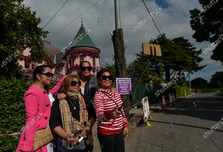 Visitors take a selfie in front of the house in The Burnaby area of Greystones which has been covered from the roof down by stretched pink flowers and trellis-style foliage ahead of Disney's 'Disenchanted' filming starting next week.On Tuesday, 8 June 2021, in Greystones, County Wicklow, Ireland.