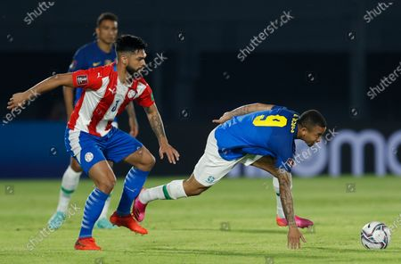 Brazil's Gabriel Jesus, right, dribbles past Paraguay's Omar Alderete during a qualifying soccer match for the FIFA World Cup Qatar 2022 at Defensores del Chaco stadium in Asuncion, Paraguay