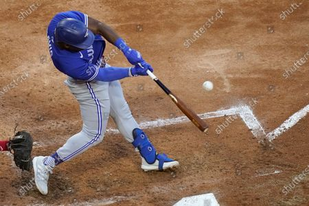 Stock Photo of Toronto Blue Jays' Jonathan Davis hits a sacrifice fly, scoring Lourdes Gurriel Jr., during the second inning of a baseball game, in Chicago