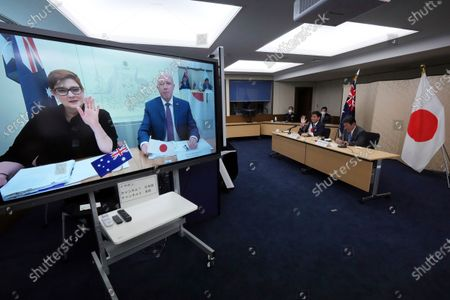 Stock Photo of Japanese Foreign Minister Toshimitsu Motegi, right, and Defense Minister Nobuo Kishi, second right, attend a video conference with Australian Foreign Minister Marise Payne, left on screen, and Australian Defense Minister Peter Dutton, right on screen, at Foreign Ministry in Tokyo during their two-plus-two ministerial meeting, in Tokyo
