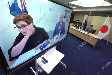 Japanese Foreign Minister Toshimitsu Motegi, right, and Defense Minister Nobuo Kishi, second right, attend a video conference with Australian Foreign Minister Marise Payne, left on screen, and Australian Defense Minister Peter Dutton, right on screen, at Foreign Ministry in Tokyo during their two-plus-two ministerial meeting, in Tokyo