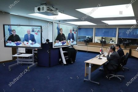 Stock Picture of Japanese Foreign Minister Toshimitsu Motegi, second right, and Defense Minister Nobuo Kishi, right, attend a video conference with Australian Foreign Minister Marise Payne, left on screen, and Australian Defense Minister Peter Dutton, right on screen, at Foreign Ministry in Tokyo during their two-plus-two ministerial meeting, in Tokyo