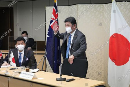 Japanese Foreign Minister Toshimitsu Motegi, right, and Defense Minister Nobuo Kishi, left, attend a video conference with Australian Foreign Minister and Minister for Women Marise Payne and Australian Defense Minister Peter Dutton at Foreign Ministry in Tokyo during their two-plus-two ministerial meeting, in Tokyo