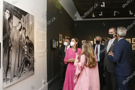 """King Felipe VI and Queen Letizia together with the Minister of Culture and Sports, José Manuel Rodríguez Uribes (L) observe a photograph during the opening of the exhibition """"Berlanguiano. Luis Garcia Berlanga (1921 -2021) """"at the Real Academia Bellas Artes de San Fernando this Wednesday. On June 9, 2021"""