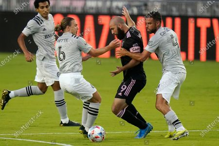 Stock Picture of Inter Miami forward Gonzalo Higuain (9) is defended by CF Montréal midfielder Samuel Piette (6) and defender Rudy Camacho (4) during the first half of a MLS soccer match, in Fort Lauderdale, Fla