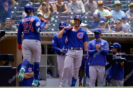 Chicago Cubs' Joc Pederson, left, jokes with teammate Patrick Wisdom, center, after hitting a home run during the fourth inning of a baseball game against the San Diego Padres, in San Diego