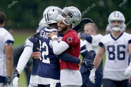Dallas Cowboys quarterback Dak Prescott (4) hugs teammate safety Jayron Kearse (32) after Kearse intercepted a pass during an NFL football team practice, in Frisco, Texas