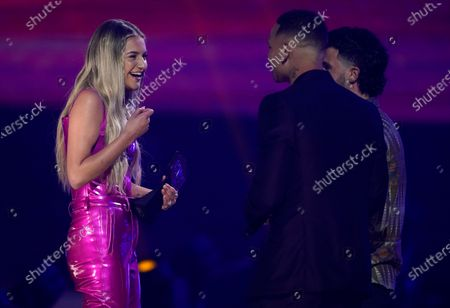 """Colton Pack of Restless Road, from right, and Kane Brown present Kelsea Ballerini with the CMT performance of the year award for """"The Other Girl"""" at the CMT Music Awards at the Bridgestone Arena, in Nashville, Tenn"""