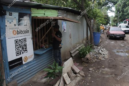 Santos Hilario Galvez, a Salvadoran who works as a builder at the Hope House, an organization that sponsors the use of cryptocurrencies in El Zonte beach, makes a purchase at a small store that accepts Bitcoin, in Tamanique, El Salvador, . El Salvador's Legislative Assembly has approved legislation making the cryptocurrency Bitcoin legal tender in the country, the first nation to do so, just days after President Nayib Bukele made the proposal at a Bitcoin conference. (AP Photo/Salvador Melendez