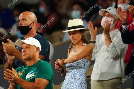 Novak Djokovic's wife Jelena Djokovic checks her watch as the curfew approaches