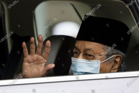 Malaysia's former Prime Minister Mahathir Mohamad, wearing a face mask, waves as he leaves the National Palace after meeting with the king in Kuala Lumpur, Malaysia