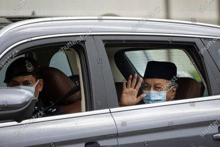 Malaysia's former Prime Minister Mahathir Mohamad, right, wearing a face mask, waves as he leaves National Palace after meeting with the king in Kuala Lumpur, Malaysia