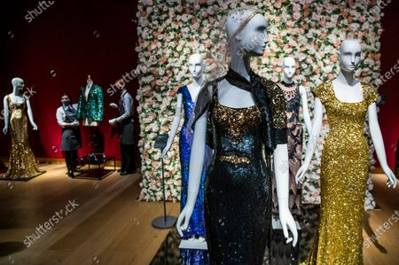 A black and gold sequined 'OSCAR' dress worn by Nicole Kidman, est £1,500-2,500 with dresses worn by Penelope Cruz and Daphne Guinness and Oak Leaf 'GLAMOUFLAGE' jacket for Mick Jagger, 2013, est £20,000-30,000, in the background - 55 lots from the archive of fashion designer L'Wren Scott. Being sold to celebrate L'Wren Scott's legacy, with the proceeds being donated to further fund the L'Wren Scott Scholarship at Central St. Martins which was set up by Mick Jagger In 2015. Previewed at Christies King Street, London.