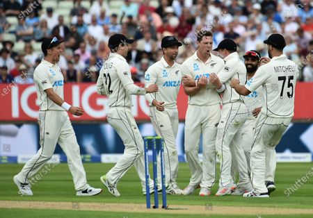 New Zealand's Matt Henry, center, celebrates with teammates the dismissal of England captain Joe Root during the first day of the second cricket test match between England and New Zealand at Edgbaston in Birmingham, England