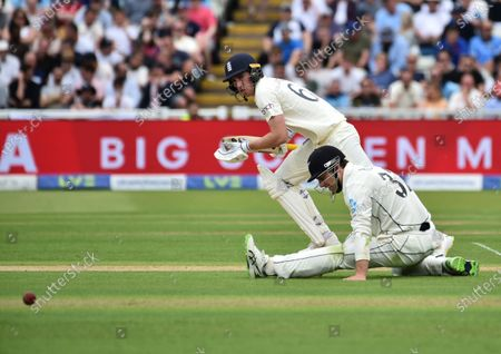 England's Dan Lawrence, left, runs past New Zealand's Will Young after playing a shot during the first day of the second cricket test match between England and New Zealand at Edgbaston in Birmingham, England