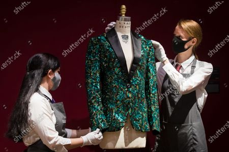 Members of staff adjust the oak leaf 'Glamouflage' jacket made for Mick Jagger at the L'Wren Scott Collection photocall at Christie's Auction House in London, Britain, 10 June 2021.