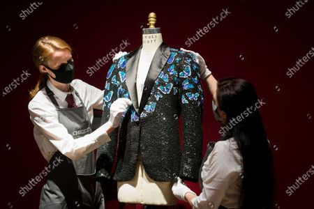 Members of staff adjust a butterfly themed jacket made for Mick Jagger at the L'Wren Scott Collection photocall at Christie's Auction House in London, Britain, 10 June 2021.