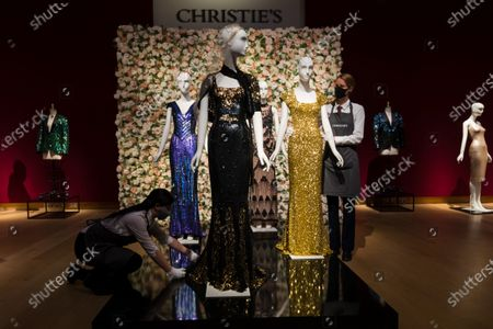 A member of staff handles a black and gold sequined 'Oscar' dress (L) worm by Nicole Kidman and gold sequined gown (R) worn by Penelope Cruz at the L'Wren Scott Collection photocall at Christie's Auction House in London, Britain, 10 June 2021.