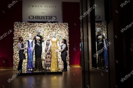 A member of staff handles a gold sequined gown worn by Penelope Cruz (R) and a blue sequinned evening gown worn by Daphne Guinness at the L'Wren Scott Collection photocall at Christie's Auction House in London, Britain, 10 June 2021.