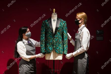 Members of staff with the oak leaf 'Glamouflage' jacket made for Mick Jagger at the L'Wren Scott Collection photocall at Christie's Auction House in London, Britain, 10 June 2021.