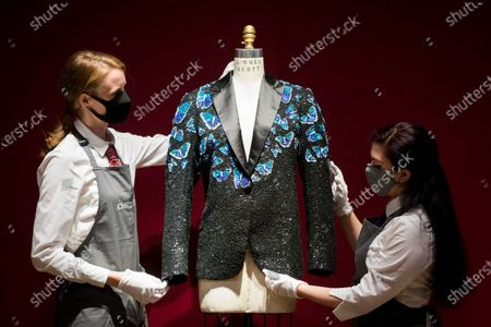 Members of staff with a butterfly themed jacket made for Mick Jagger at the L'Wren Scott Collection photocall at Christie's Auction House in London, Britain, 10 June 2021.