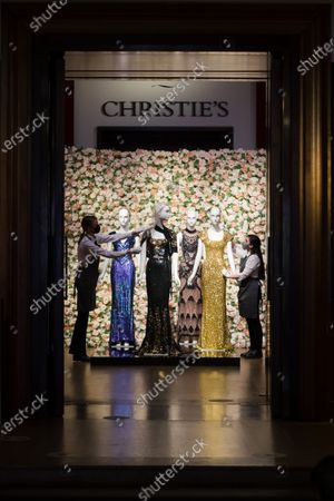 A member of staff handles a black and gold sequined 'Oscar' dress worm by Nicole Kidman (L) and gold sequined gown worn by Penelope Cruz (R) at the L'Wren Scott Collection photocall at Christie's Auction House in London, Britain, 10 June 2021.
