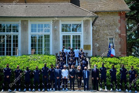 French President Emmanuel Macron, center, France's coach Didier Deschamps, center left, French President's wife wife Brigitte Macron, center right, French Football Federation (FFF) president Noel Le Graet, sixth right, and FIFA president Gianni Infantino, fifth right, pose for a group picture with France's players before a lunch at the national soccer training camp in Clairefontaine-en-Yvelines, ahead of the UEFA EURO 2020 soccer tournament
