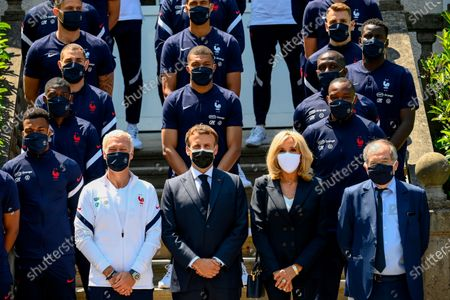 French President Emmanuel Macron, center, France's coach Didier Deschamps, center left, French President's wife wife Brigitte Macron, center right, French Football Federation (FFF) president Noel Le Graet, right, pose for a group picture with France's players before a lunch at the national soccer training camp in Clairefontaine-en-Yvelines, ahead of the UEFA EURO 2020 soccer tournament