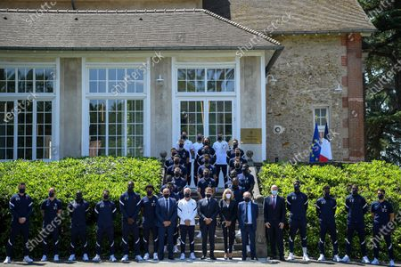 French President Emmanuel Macron (C), France's coach Didier Deschamps (C-L), French President's wife wife Brigitte Macron (C-R), French Football Federation (FFF) president Noel Le Graet (6-R) and FIFA president Gianni Infantino (5-R) pose for a group picture with France's players befor a lunch in Clairefontaine-en-Yvelines, France, 10 June 2021, ahead of the UEFA EURO 2020 football competition.