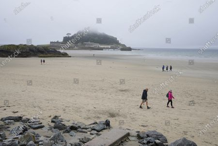 Mist settles over St. Michael's Mount as people walk on the beach during preparations for the G7 Summit in Mount's Bay, Cornwall, England, . G7 leaders and guests will meet in the the Cornish resort of Carbis Bay in St. Ives starting Friday, June 11, 2021