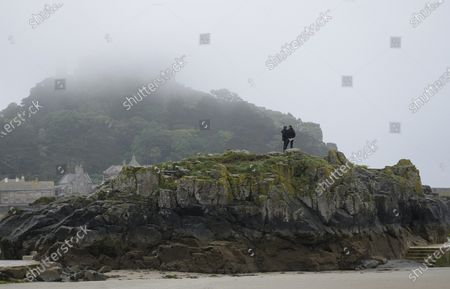 Stock Image of Mist settles over St. Michael's Mount as people walk on the rocks at Mount's Bay, Cornwall, England, . G7 leaders and guests will meet in the the Cornish resort of Carbis Bay in St. Ives starting Friday, June 11, 2021