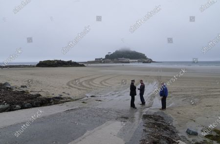 Mist settles over St. Michael's Mount as police walk on the beach during preparations for the G7 Summit in Mount's Bay, Cornwall, England, . G7 leaders and guests will meet in the the Cornish resort of Carbis Bay in St. Ives starting Friday, June 11, 2021