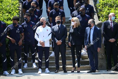 French President Emmanuel Macron, France's coach Didier Deschamps, center left, French President's wife Brigitte Macron, center right, French Football Federation (FFF) president Noel Le Graet, second right, and FIFA president Gianni Infantino, right, pose for a group picture with France's players before a lunch at the national soccer training camp in Clairefontaine-en-Yvelines, Thursday June 10, 2021 ahead of the UEFA EURO 2020 soccer tournament.