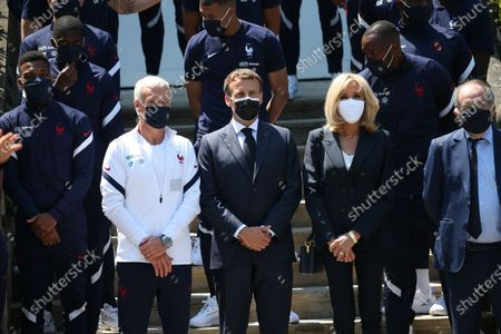 French President Emmanuel Macron, center left, French President's wife Brigitte Macron, center right, French Football Federation (FFF) president Noel Le Graet, right, pose for a group picture with France's players before a lunch at the national soccer training camp in Clairefontaine-en-Yvelines, Thursday June 10, 2021 ahead of the UEFA EURO 2020 soccer tournament.