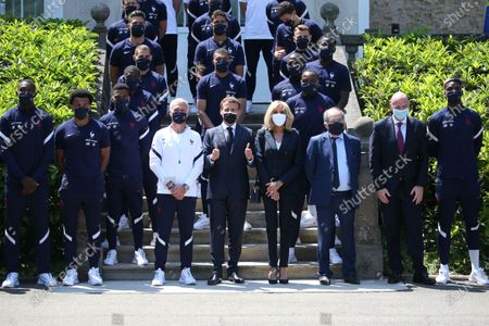 French President Emmanuel Macron, France's coach Didier Deschamps, center left, French President's wife Brigitte Macron, center right, French Football Federation (FFF) president Noel Le Graet, sixth right, and FIFA president Gianni Infantino, fifth right, pose for a group picture with France's players before a lunch at the national soccer training camp in Clairefontaine-en-Yvelines, Thursday June 10, 2021 ahead of the UEFA EURO 2020 soccer tournament.