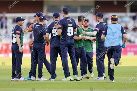 Laurie Evans of Surrey hits the ball and is caught by Luke Hollman of Middlesex who celebrates with his team mates during the Vitality T20 Blast South Group match between Middlesex County Cricket Club and Surrey County Cricket Club at Lord's Cricket Ground, St John's Wood