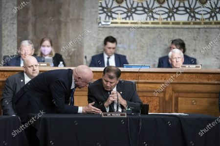 """Stock Picture of Senator Mark Kelly, D-AZ, speaks with Senator Mike Rounds, R-SD, during a Senate Armed Services Committee hearing at the U.S. Capitol in Washington DC, on Thursday, June 10, 2021. The committee heard testimony on the """"Defense Department budget posture in review of the Defense Authorization Request for FY2022."""""""