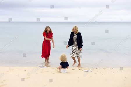 Carrie Johnson, the wife of Prime Minister Boris Johnson, speaks with First Lady of the United States Dr. Jill Biden as Wilfred Johnson sits on the beach during the G7 Leaders' Summit in Carbis Bay, Cornwall, United Kingdom, on June 10, 2021.